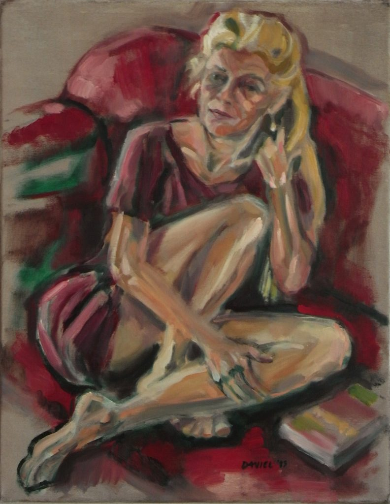 Woman with legs folded sitting on a red sofa